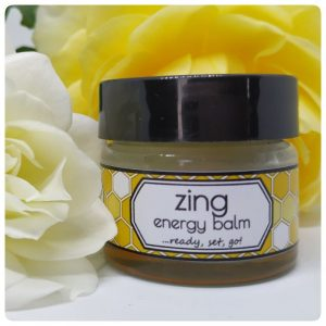 15g jar with an orange label in front of white and yellow roses