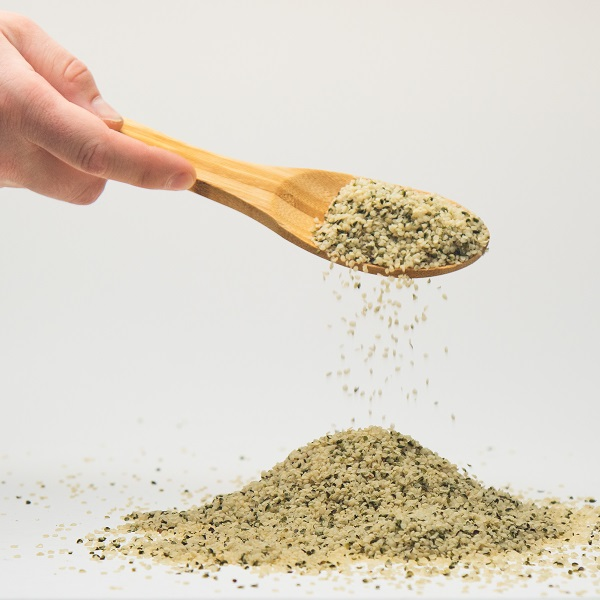 Hand scooping up hemp hearts from a pile of hemp hearts with a wooden spoon